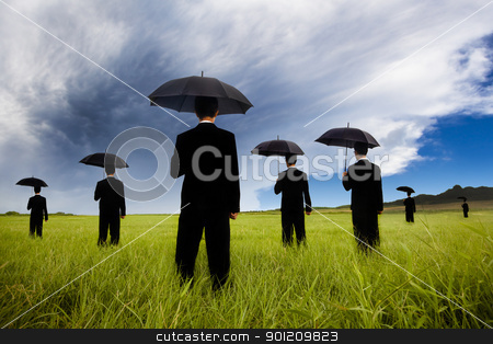 businessman in black suit  holding umbrella and watching the storm coming