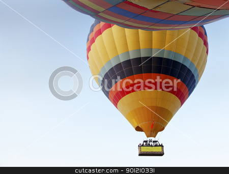 abstract two hot air balloons light blue sky stock photo, landscape concept of two multi colored hot air balloons in a clear light blue sky with a basket of passengers by Kantilal Patel
