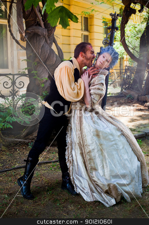 vampire attacking medieval woman stock photo, Male vampire biting woman's neck, both dressed in medieval costumes by vilevi