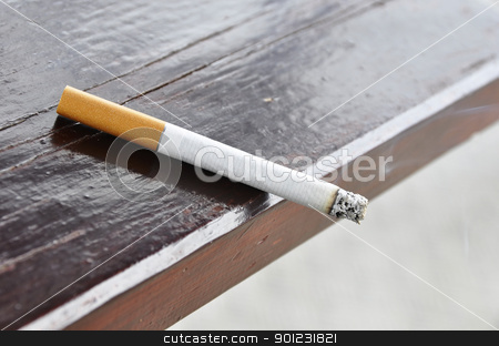 A cigarette stock photo, A cigarette on a wood table by Dutourdumonde