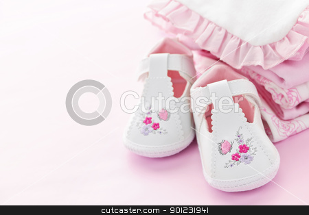 Pink baby clothes for infant girl stock photo, Infant girl clothing and shoes for baby shower on pink background by Elena Elisseeva