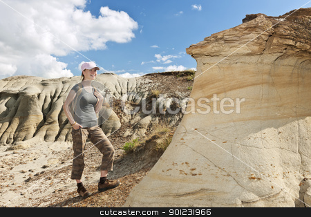 Hiker in badlands of Alberta, Canada stock photo, Teenage girl standing near hoodoos in Dinosaur provincial park, Alberta, Canada by Elena Elisseeva