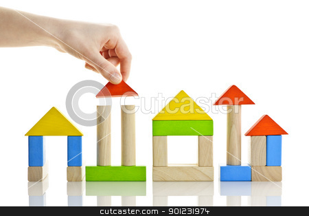 Building with wooden blocks stock photo, Hand building houses of wooden block toys isolated on white background by Elena Elisseeva