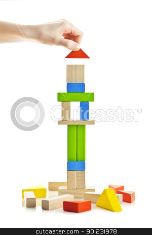Wooden block tower under construction stock photo, Hand building tower of wooden blocks isolated on white background by Elena Elisseeva