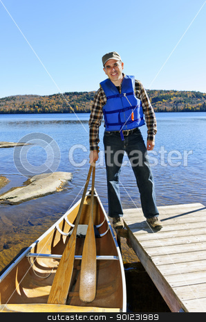 Man with canoe stock photo, Man standing on dock with canoe on Lake of Two Rivers, Ontario, Canada by Elena Elisseeva