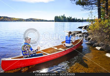 Canoeing near lake shore stock photo, Family in red canoe near rocky shore of Lake of Two Rivers, Ontario, Canada by Elena Elisseeva