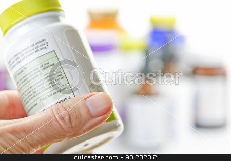 Hand holding medicine bottle stock photo, Hand holding medicine bottle to read label by Elena Elisseeva