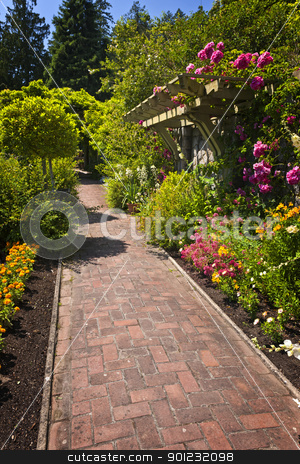 Flower garden with paved path stock photo, Lush summer garden with paved path and blooming flowers by Elena Elisseeva