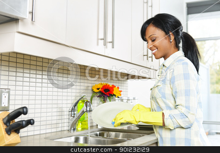 Young woman washing dishes stock photo, Smiling young black woman washing dishes in kitchen by Elena Elisseeva
