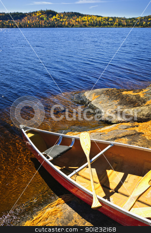 Canoe on shore stock photo, Red canoe on rocky shore of Lake of Two Rivers, Ontario, Canada by Elena Elisseeva