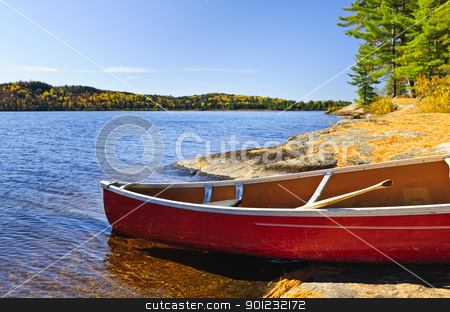 Red canoe on shore stock photo, Red canoe on rocky shore of Lake of Two Rivers, Ontario, Canada by Elena Elisseeva