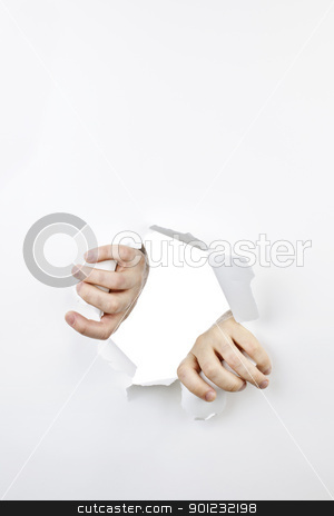 Hands ripping through hole in paper stock photo, Hands ripping a hole in white paper with torn edges by Elena Elisseeva