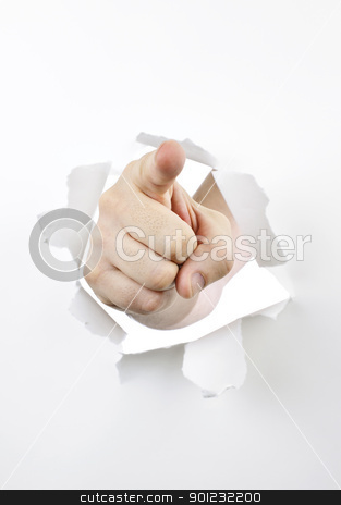 Finger pointing through hole in paper stock photo, Finger pointing through hole torn in white paper by Elena Elisseeva