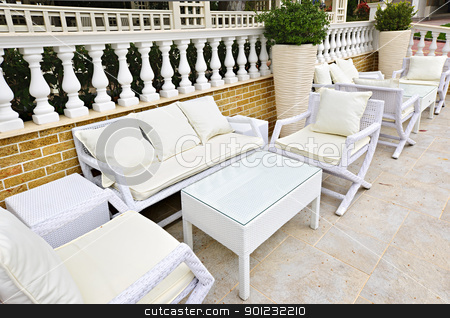 Patio furniture outdoor stock photo, Wicker patio furniture outdoor in area paved with natural stone by Elena Elisseeva