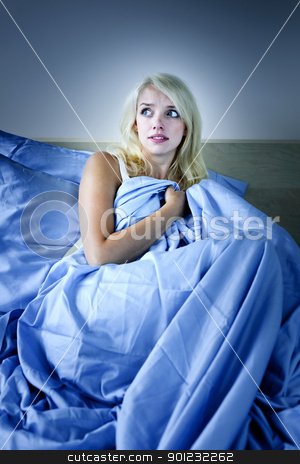 Woman scared in bed stock photo, Sleepless blonde woman scared at night in bed by Elena Elisseeva