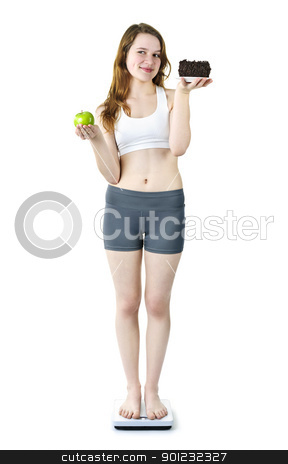 Young girl on scale holding apple and cake stock photo, Tempted young woman holding apple and chocolate cake standing on scale by Elena Elisseeva