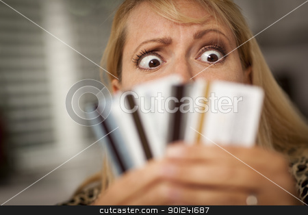 Upset Woman Glaring At Her Many Credit Cards stock photo, Upset Robed Woman Glaring At Her Many Credit Cards. by Andy Dean