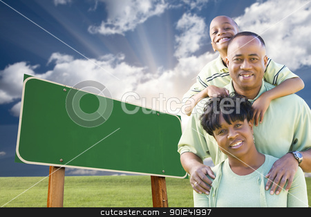 African American Family in Front of Blank Green Road Sign stock photo, Attractive African American Family in Front of Blank Green Road Sign Ready for Your Own Message. by Andy Dean