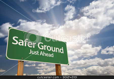 Safer Ground Green Road Sign stock photo, Safer Ground Green Road Sign Against Dramatic Sky, Clouds and Sunburst. by Andy Dean