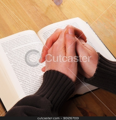 pray stock photo, praying hand and book on desk showing religion concept by Gunnar Pippel