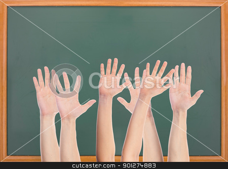 Many hands and blank blackboard stock photo, Many hands rise in front of blank blackboard by Lawren