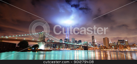 New York City panorama stock photo, Remember September 11. New York City Manhattan panorama view with Brooklyn Bridge at night with office building skyscrapers skyline illuminated over Hudson River and two light beam in memory of September 11. by rabbit75_cut