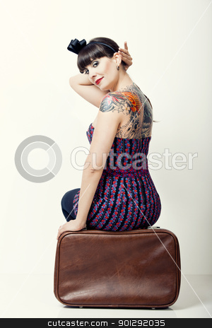 Vintage woman stock photo, Close-uo portrait of a beautiful woman with a vintage style sitting on a bag by ikostudio