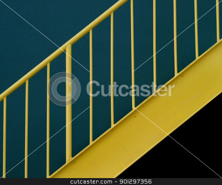 Yellow Metal Staircase stock photo, A yellow metal stairway with a green background by Tyler Olson