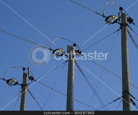 Power Poles stock photo, Three power poles stand against a blue sky. by Tyler Olson