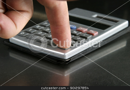 Calculator Detail stock photo, Small personal calculator detail with a finger pressing the equals sign by Tyler Olson