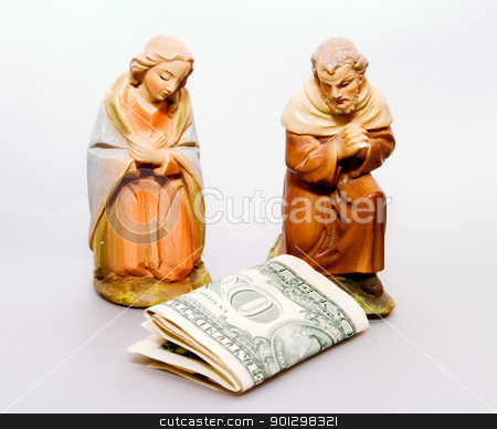 Commercial Nativity stock photo, Commercialism vs Christmas, a vintage Mary and Joseph look down at an american dollar bill. by Tyler Olson