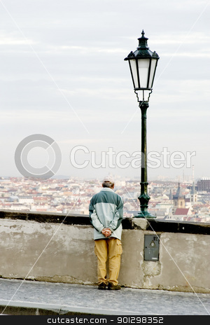 Looking Thinking stock photo, Prague, Czech Republic cityscape seen from the Prague castle with an elderly man looking out over the horizon. by Tyler Olson