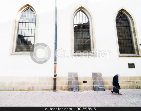 Old Woman Abstract stock photo, An abstract image of an old woman hunched over walking by a large church (Betlemske Nam) with tall gothic windows in Prague, Czech Republic. by Tyler Olson