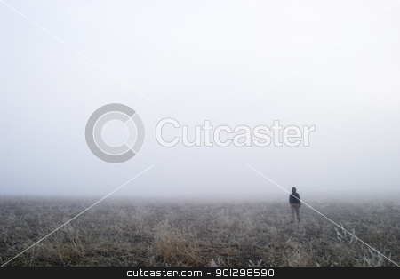 Fog Walk stock photo, A person walking in the fog, disappearing into the distance. by Tyler Olson