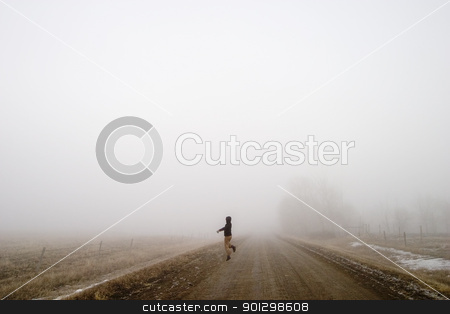 Happy in the Fog stock photo, Walking alone on a saskatchewan road in the fog with a skip of joy by Tyler Olson