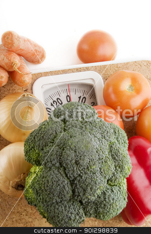 Weight Loss stock photo, Garden vegetables on a bathroom scale by Tyler Olson