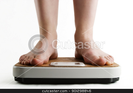 Weighing In stock photo, A pair of female feet standing on a bathroom scale by Tyler Olson