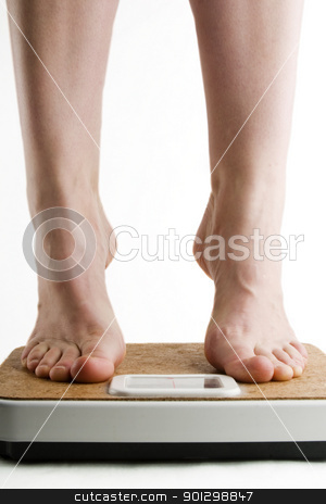 Weighing In stock photo, A pair of female feet standing on tip toe on a bathroom scale by Tyler Olson