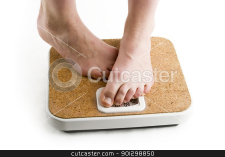 Weighing In stock photo, A pair of female feet standing on a bathroom scale looking shy about the weight by Tyler Olson