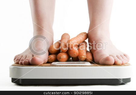 Healthy Living stock photo, A pair of female feet standing on a bathroom scale with a pile of carrots between them. by Tyler Olson