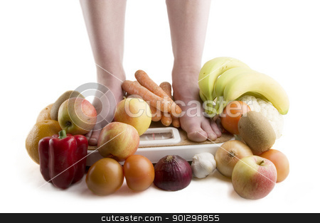 Diet stock photo, A pair of female legs standing on a scale surrounded by fruits and vegetables. by Tyler Olson
