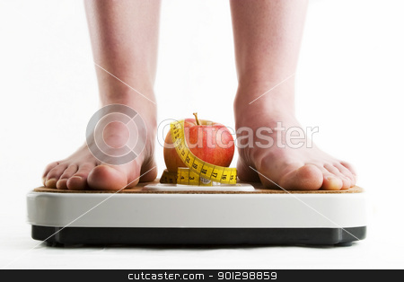 Diet stock photo, A pair of female feet standing on a bathroom scale with an apple and tape measure between them. by Tyler Olson