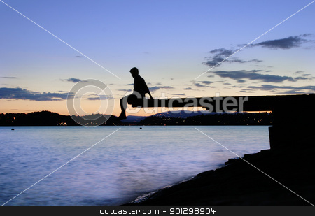 Dock at Dusk stock photo, A young person sitting on a dock at dusk, at the fjord in Oslo, Norway by Tyler Olson