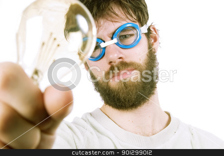 Funny Idea stock photo, A concept image protraying a funny / good idea.  A young funny looking bearded male with swimming goggles holding up a light bulb. by Tyler Olson