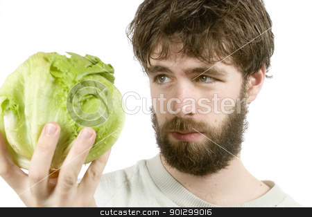 Salad Sceptic stock photo, A young male with a beard looking at salad with scepticism.  The salad is out of focus. by Tyler Olson