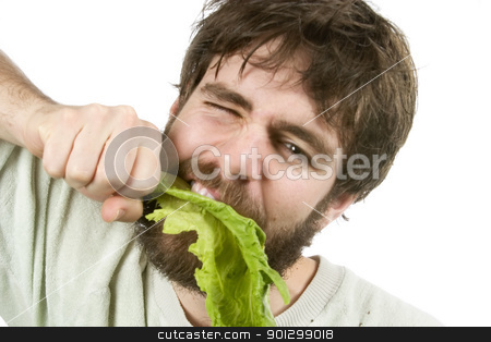 Eager Salad Eater stock photo, A young male with a beard is eagerly eating salad, as if he were a barbarian eating meat. by Tyler Olson