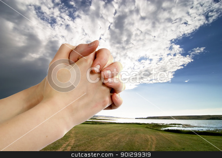 Prayer stock photo, A pair of hands in a praying position set against a beautiful prairie lake landscape by Tyler Olson