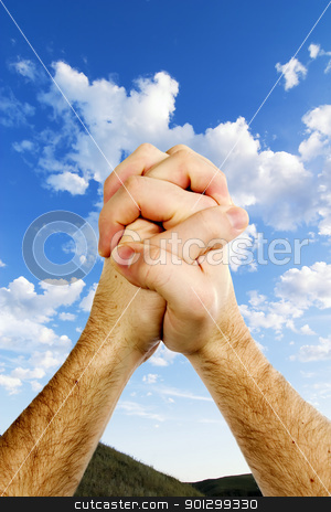 Beautiful Prayer stock photo, Praying hands on top of a beautiful prairie landscape with a deep blue sky and picturesque clouds. by Tyler Olson