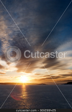 Sunset on Frozen Lake stock photo, A golden sunset going down behind a hill over a frozen lake - fjord.  Oslo fjord in March. by Tyler Olson