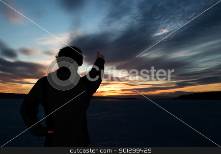 Man on Frozen Lake stock photo, A man standing on the edge of a frozen lake at sundown by Tyler Olson